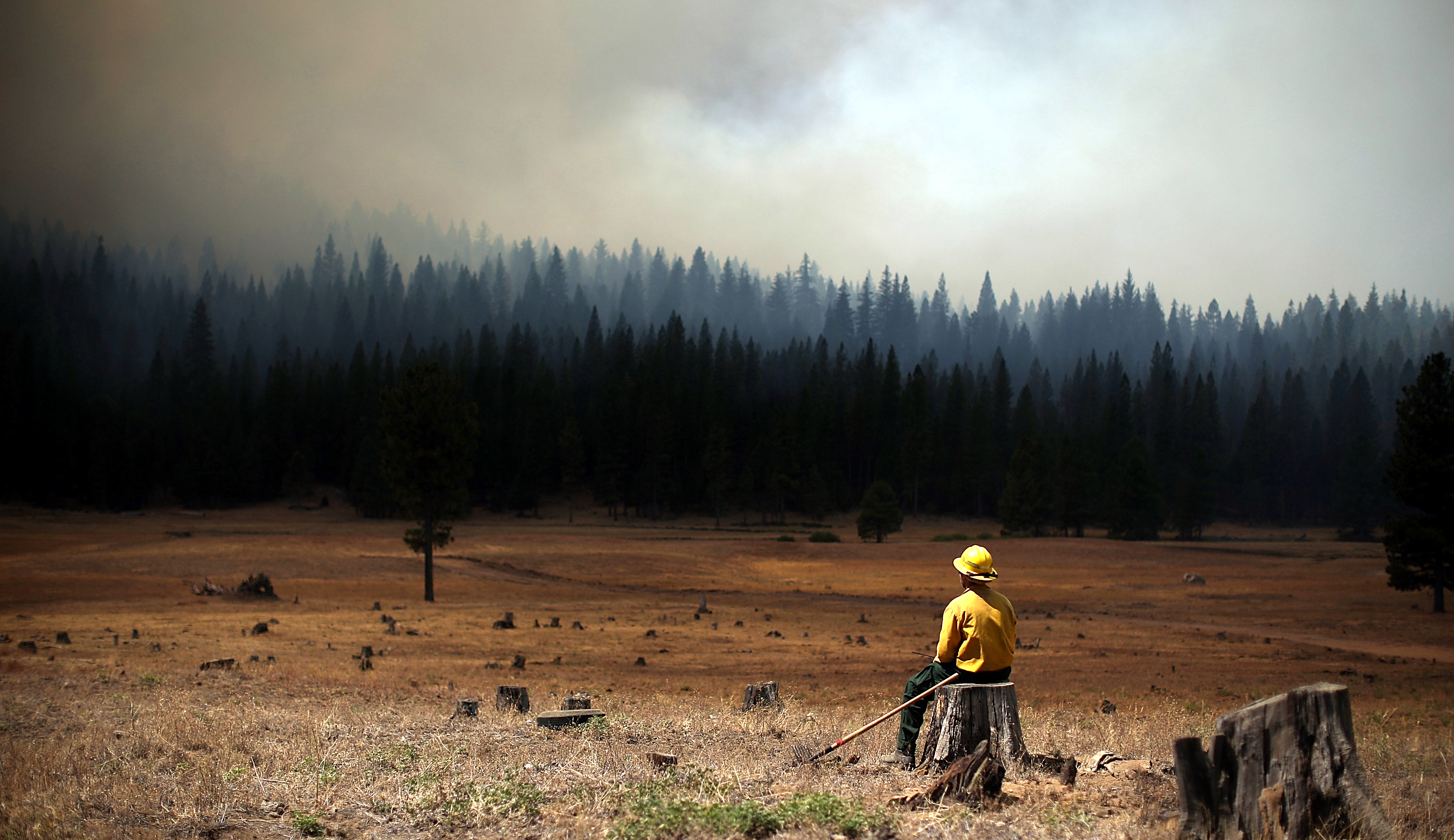 A U.S. Fish and Wildlife Service firefighter monitors the Rim Fire on Aug. 25, 2013 near Groveland, Calif.