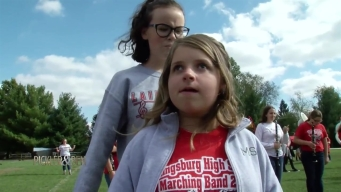Student Leads Blind Classmate in Band Marches