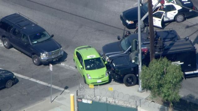 Police in armored vehicles pin a taxi driven by a suspected carjacker who led police on a two-hour chase in South Los Angeles on Friday, April 10, 2015.