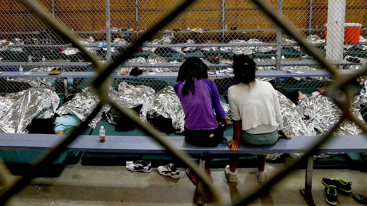 Two young girls watch a World Cup soccer match on a television from their holding area where hundreds of mostly Central American immigrant children are being processed and held at the U.S. Customs and Border Protection Nogales Placement Center on June 18, 2014, in Nogales, Arizona.