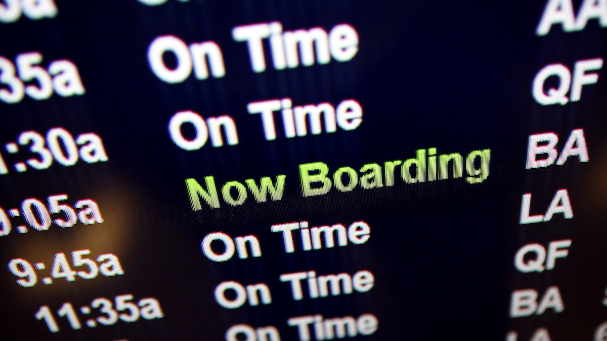 A schedule board indicates mostly On Time flights as another is