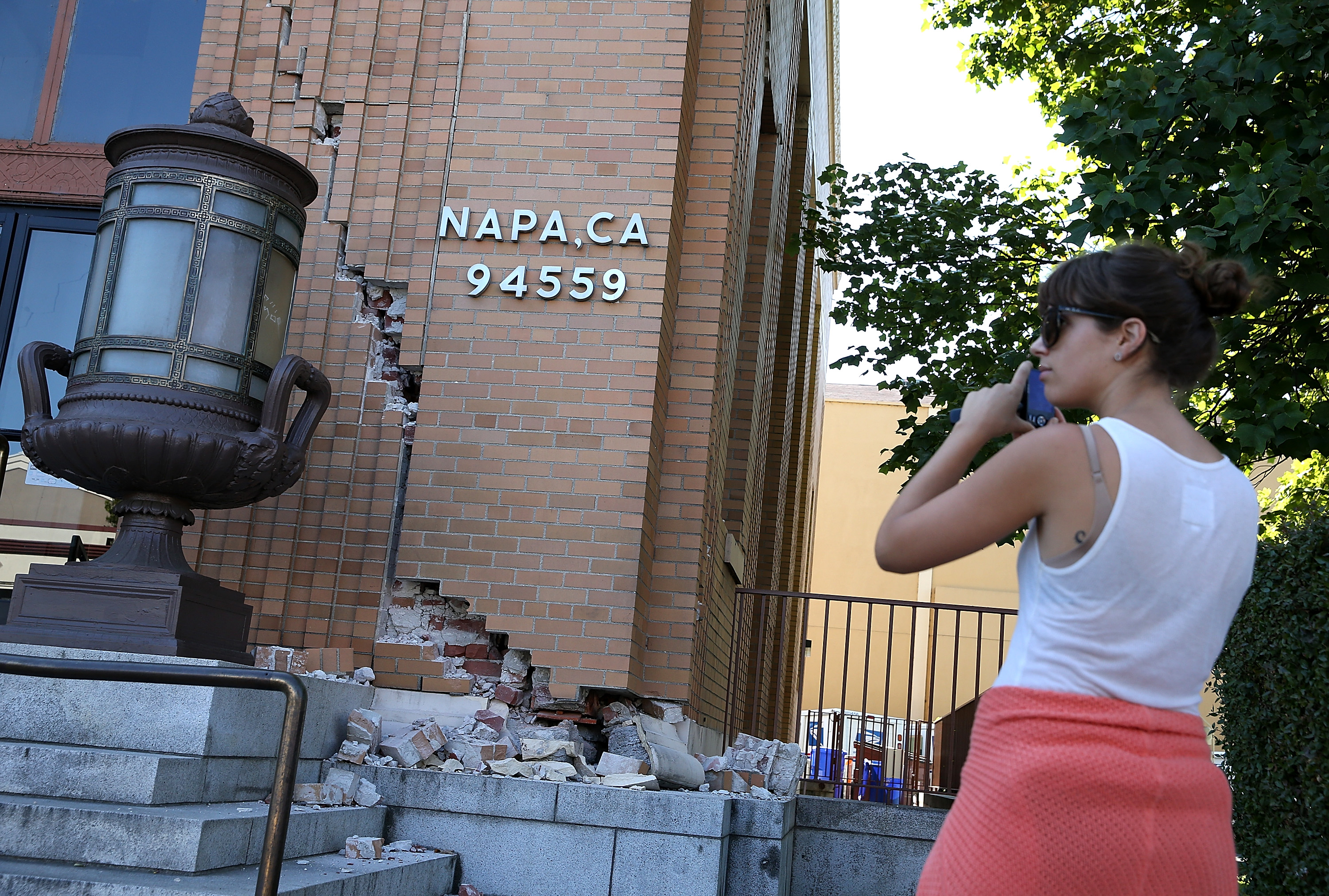 NAPA, CA - AUGUST 24:  A passerby stops to take a picture of damage to the Napa post office following a reported 6.0 earthquake on August 24, 2014 in Napa, California.  A 6.0 earthquake rocked the San Francisco Bay Area shortly after 3:00 am on Sunday morning causing damage to buildings and sending at least 70 people to a hospital with non-life threatening injuries.  (Photo by Justin Sullivan/Getty Images)