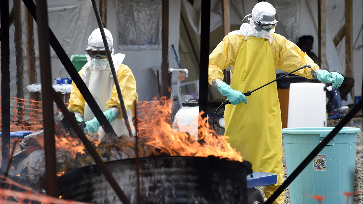 FILE - Medical staff members burn clothes belonging to patients suffering from Ebola, at the French medical NGO Medecins Sans Frontieres (MSF) in Monrovia on September 27, 2014. Liberia welcomed global pledges of action on the Ebola epidemic ravaging west Africa, admitting on Sept. 26 that the government was losing the trust of its people with the outbreak still out of control.