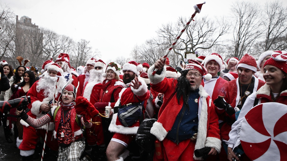 NEW YORK, NY - DECEMBER 14: Revelers dressed as Santa Claus pose for a picture at Tompkins Square Park to take part during the annual SantaCon bar crawl event on December 14, 2013 in New York City. The SantaCon annual event occurs worldwide in more than 300 cities in 44 countries. In New York some community groups have established a 'Santa Free' zone that urges bars not to serve alcoholic beverages to people participating in order to dissuade incidents of public vomiting and urination in the streets. (Photo by Kena Betancur/Getty Images)
