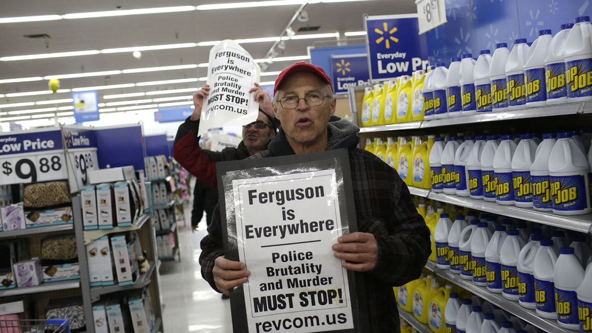 Demonstrators protesting the shooting death of Michael Brown hold signs as they walk through a local Walmart store on Black Friday, November 28, 2014 in Ferguson, Missouri.