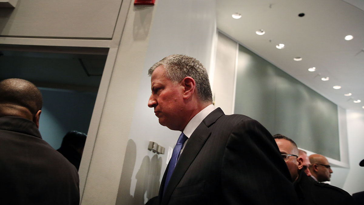 New York Mayor Bill de Blasio leaves a news conference at Woodhull Hospital following the killing of two New York City police officers on December 20, 2014 in New York City.