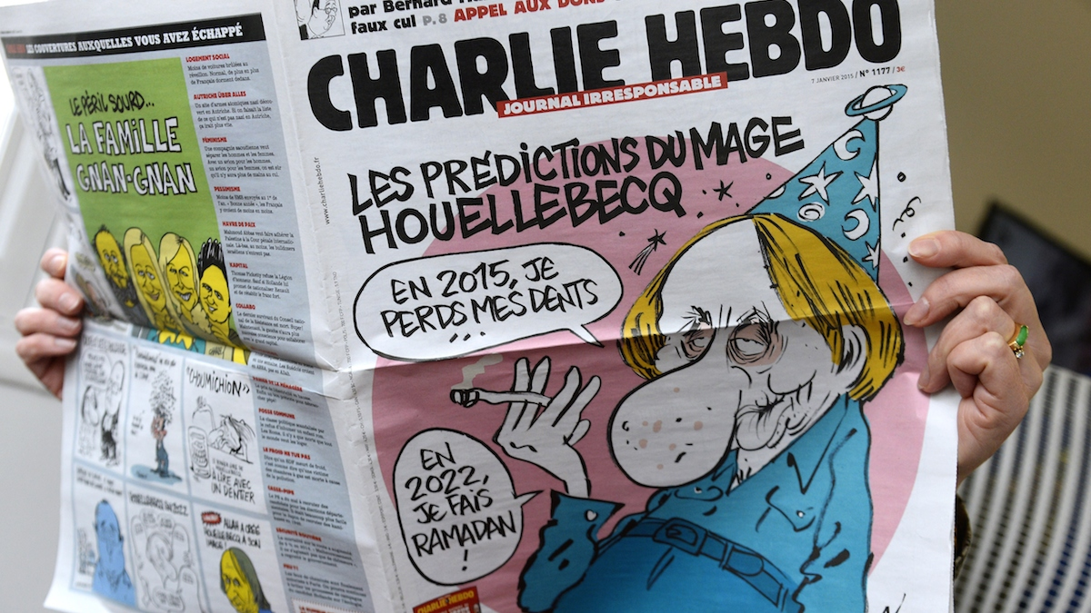 A person reads the latest issue of the French satirical newspaper Charlie Hebdo in Paris on January 7, 2015, after gunmen armed with Kalashnikovs and a rocket-launcher opened fire in the offices of the weekly in Paris, killing 12.
