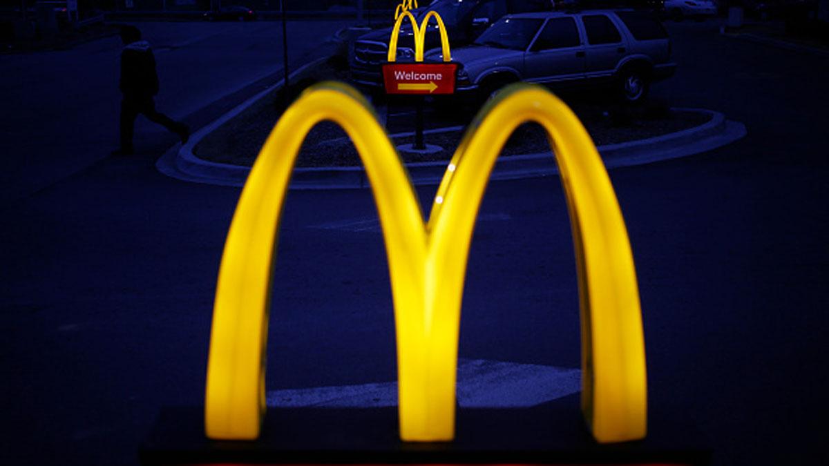 Illuminated golden arches mark the entrance to a McDonald's restaurant.