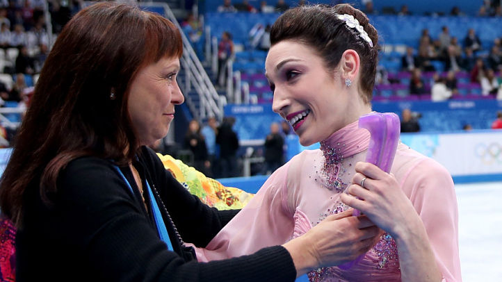 Meryl Davis and Charlie White of the United States are welcomed by their coach Marina Zoueva after competing during the figure skating ice dance short dance on Day 9 of the Sochi 2014 Winter Olympics at Iceberg Skating Palace on February 16, 2014 in Sochi, Russia.