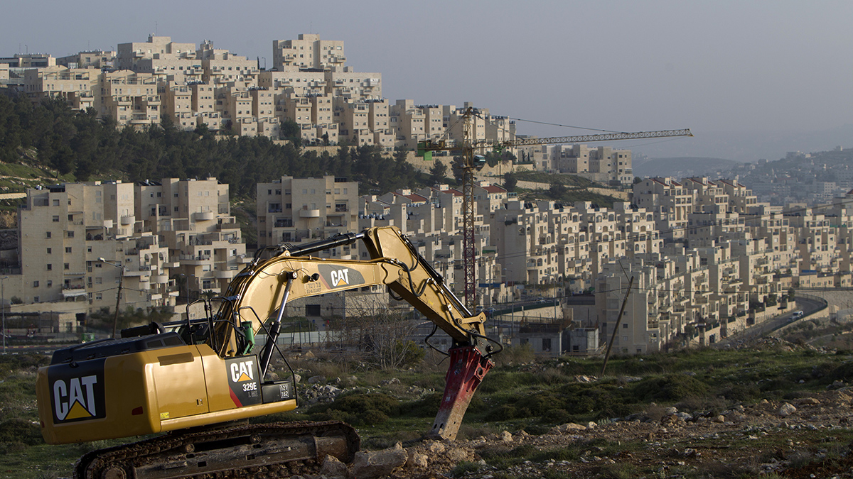 In this file photo, a bulldozer is seen next to a new housing construction site in the Israeli settlement of Har Homa (background) in east Jerusalem on March 19, 2014. In an unprecedented diplomatic rebuke of Israel, the United States abstained Friday on a United Nations Security Council resolution demanding an end to Israeli settlements, allowing the measure to pass.