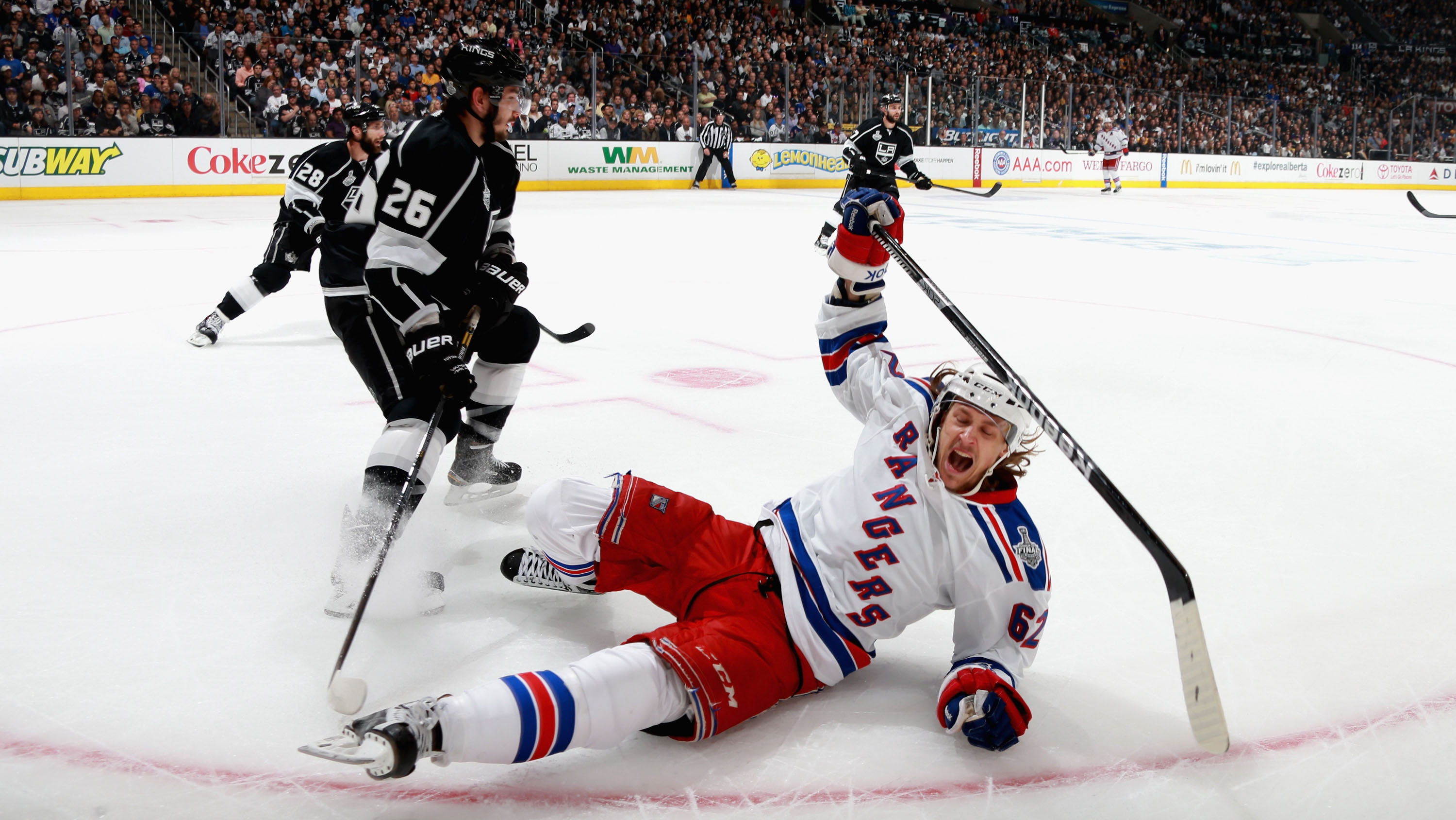 Carl Hagelin #62 of the New York Rangers falls to the ice in the second period of Game One of the 2014 Stanley Cup Final against the Los Angeles Kings at Staples Center on June 4, 2014 in Los Angeles, California. The Los Angeles Kings beat the New York Rangers 3-2.  Click through to see more from the game.