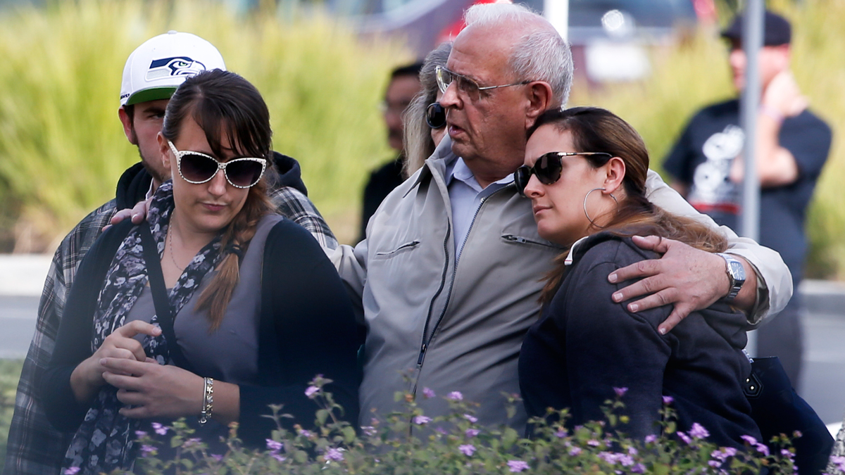 One week after the mass shooting at the Inland Regional Center in San Bernardino, the families and loved ones of the victims were allowed to stand outside the building for a quiet look December 9, 2015. Escorted by police motorcycles, two charter buses arrived, unloaded and left shortly the people snapped photos and exchanged hugs.