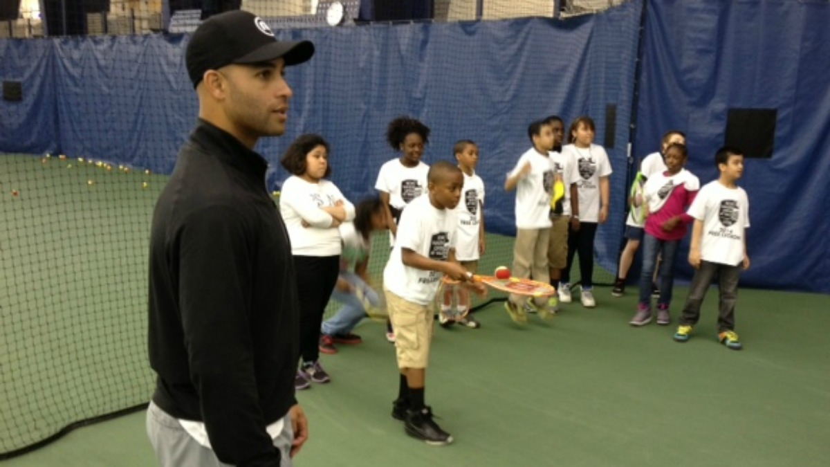 Tennis pro James Blake gives tennis lessons to New Haven students.