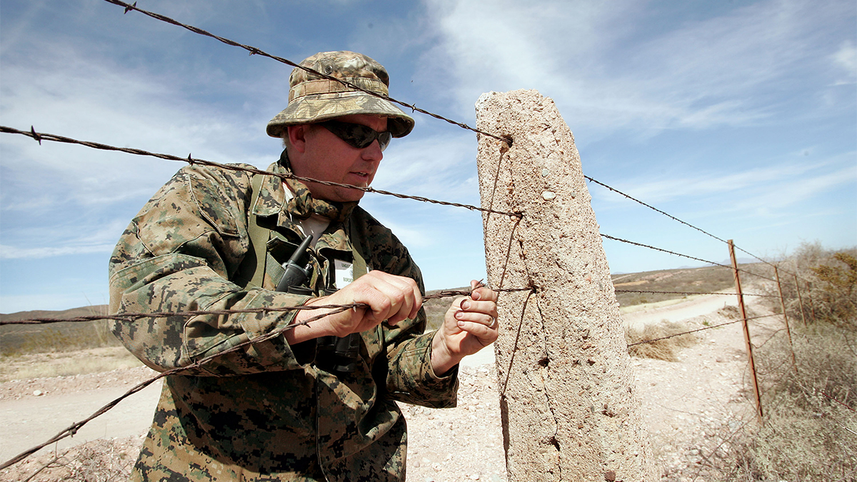 NACO, AZ - APRIL 2:  A Minuteman volunteer repairs a hole in the barbed wire fence which separates the United States and Mexico April 2, 2005 near Naco, AZ. More than 1,000 volunteers from the Minuteman Project are expected to fan out across a 23 mile stretch on the Arizona side of the border to search for Illegal aliens who are making the trek into the United States from Mexico during April.  (Photo by Scott Olson/Getty Images)