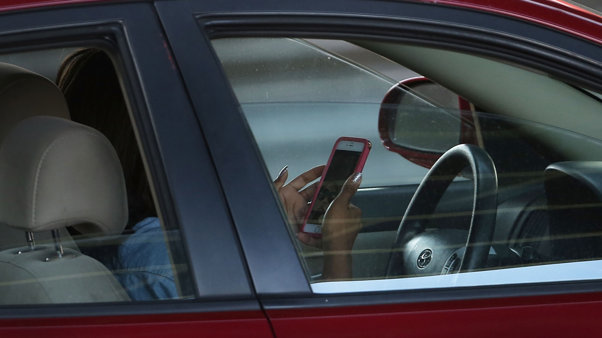 A driver uses a phone while behind the wheel of a car on April 30, 2016, in New York City. As accidents involving drivers using phones or other personal devices mount across the country, New York lawmakers have proposed a new test called the Textalyzer to help curb mobile phone usage behind the wheel. Similar to a Breathalyzer test, the Textalyzer would allow police to request phones from drivers involved in accidents and then determine if the phone had been used while the drivers operated their vehicles. The controversial bill is currently in the early committee stage. According to statistics, In 2014 431,000 people were injured and 3,179 were killed in car accidents involving distracted drivers. (Photo by Spencer Platt/Getty Images)