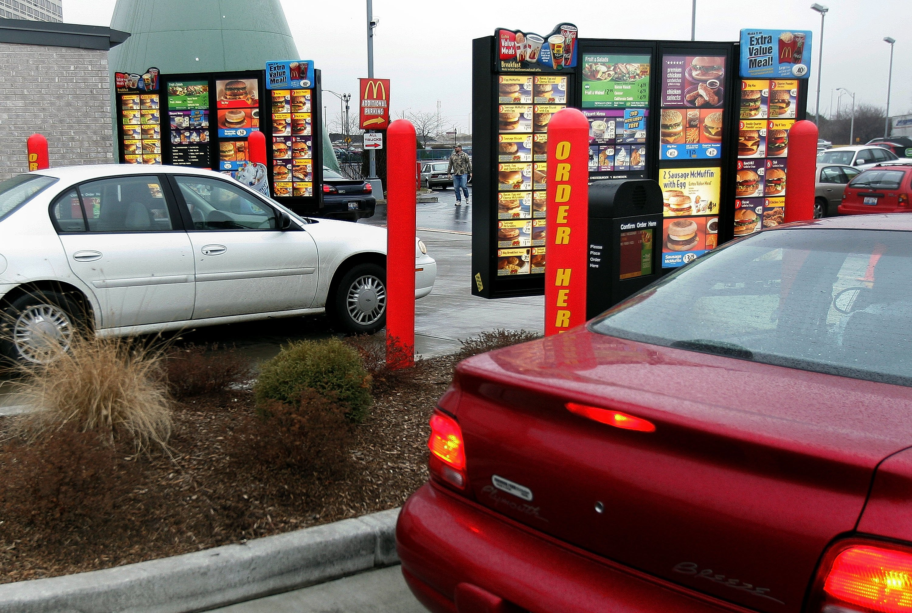 Vehicles in two separate drive-up lanes place orders at a McDonald's drive-thru location January 17, 2006 in Rosemont, Illinois. McDonald's, reportedly in an effort to satisfy consumers in a hurry for food-to-go and traffic related to such, has built dual drive-ups at some of their restaurants. (Photo by Tim Boyle/Getty Images)