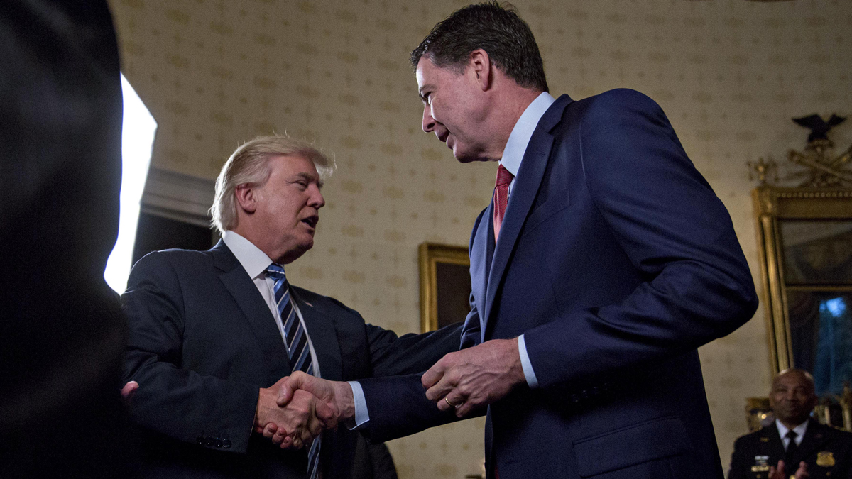 This Jan. 22, 2017, file photo shows President Donald Trump shaking hands with then-FBI Director James Comey at a reception in the White House in Washington, D.C. Trump would later fire Comey, calling him a