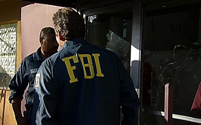 An FBI agent and an LAPD officer on Thursday, Feb. 28, 2013 investigate the scene of an apartment in North Hollywood, where Ammar Harris, the suspect in a Las Vegas triple slaying, was believed to have been hiding out.