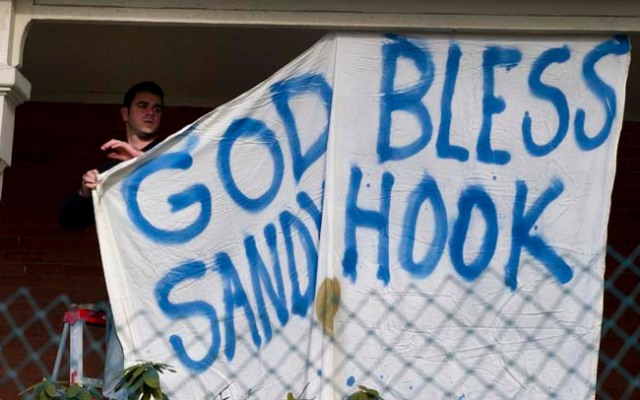 A man hangs a sign on the front of his home near Sandy Hook Elementary School Dec.15, 2012 in Newtown, Conn.