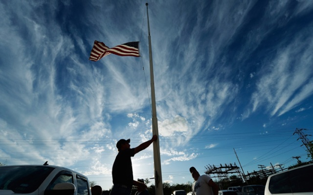 Bill Warren, a member of Veterans of Foreign Wars Post 4819, lowers the U.S. flag to half staff in memory of victims of the West Fertilizer Company explosion April 18, 2013 about 20 miles north of Waco in West, Texas.  (Photo by Kevork Djansezian/Getty Images)
