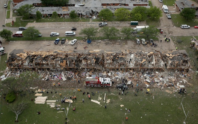 Search and rescue workers comb through what remains of a 50-unit apartment building (foreground) and the West Rest Haven Nursing Home the day after an explosion at the West Fertilizer Company destroyed the buildings April 18, 2013 in West, Texas. According to West Mayor Tommy Muska, around 14 people, including 10 first responders, were killed and more than 150 people were injured when the fertilizer company caught fire and exploded, leaving damaged buildings for blocks in every direction.  (Photo by Chip Somodevilla/Getty Images)