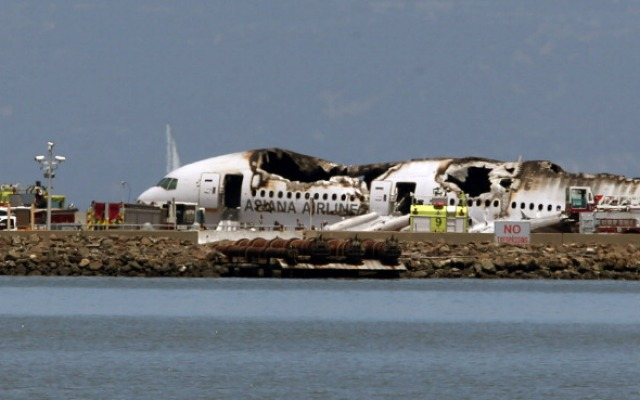 A Boeing 777 airplane lies burned on the runway after it crashed landed at San Francisco International Airport July 6, 2013 in San Francisco, California.