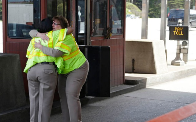 Toll taker Dawnette Reed, left, is embraced by co-worker Marsha Brandhorst, right, at the end of her shift on the Golden Gate Bridge Tuesday, March 26, 2013 in San Francisco.