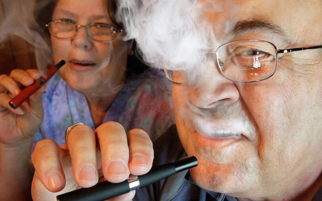 Cliff Phillips, a 61-year-old retiree and former smoker, and his wife, Vali, enjoy electronic cigarettes at their home in Cuba, Ill. Electronic cigarettes like the one used by Phillips are at the middle of a social and legal debate over whether it's OK to