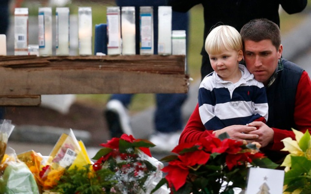 A man holds a child while paying respects to shooting victims at a makeshift memorial outside of St. Rose of Lima Roman Catholic Church, Sunday, Dec. 16, 2012, in Newtown, Conn. On Friday, a gunman killed his mother at their home and then opened fire inside the Sandy Hook Elementary School in Newtown, killing 26 people, including 20 children.(AP Photo/Julio Cortez)