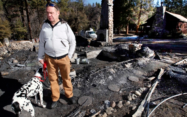 In this Friday Feb. 15, 2013 file photo, Rick Heltebrake with his dog Suni looks over the burned-out cabin where Christopher Dorner's remains were found after a police standoff Tuesday near Big Bear, Calif. Heltebrake, a ranger who takes care of a Boy Scout camp, intends to sue the city of Los Angeles for $1 million in reward money for helping lead police to Dorner. (AP Photo/Nick Ut, FIle)