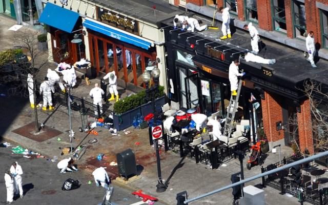 Investigators comb through the scene of one of the blast sites of the Boston Marathon explosions, Wednesday, April 17, 2013, in Boston. (AP Photo/Julio Cortez)