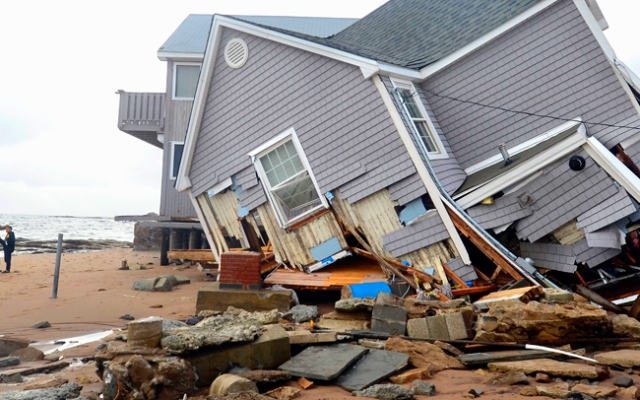 People stand next to a house collapsed from superstorm Sandy in East Haven, Conn. on Tuesday, Oct. 30, 2012. (AP Photo/Jessica Hill)