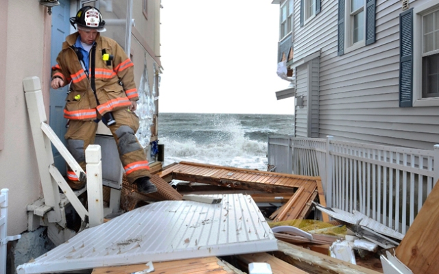 Milford Fire Department Capt. Christopher Waiksnoris checks for residents during another evacuation due to high tide in Milford, Conn., Tuesday, Oct. 30, 2012. Superstorm Sandy made landfall Monday, and caused multiple fatalities, halted mass transit and cut power to more than 6 million homes and businesses. (AP Photo/Jessica Hill)
