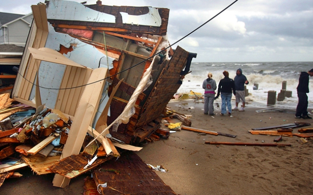 People walk near a storm-damaged home along the waterfront in the aftermath of Sandy on Tuesday, Oct. 30, 2012, in Milford, Conn. Sandy, the storm that made landfall Monday, caused multiple fatalities, halted mass transit and cut power to more than 6 million homes and businesses. (AP Photo/The Connecticut Post, Brian A. Pounds) MANDATORY CREDIT