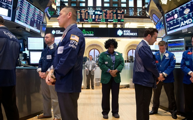 In this photo provided by the New York Stock Exchange Euronext, employees of the NYSE observe a moment of silence on the floor of the exchange in New York, Monday, April 22, 2013, a week after bombs exploded at the finish line of of the Boston Marathon.