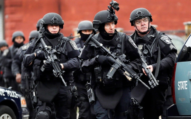 Police in tactical gear conduct a search for a suspect in the Boston Marathon bombings, Friday, April 19, 2013, in Watertown, Mass. T