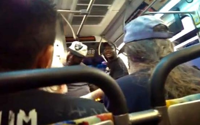A Los Angeles Metro passenger, wearing a white hat, appears to berate an older commuter, apparently because he sat on him while trying to take a seat on a packed bus.