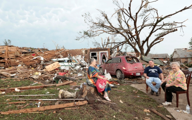 MOORE, OK - MAY 20:  (L - R) Yvonne Barragar, Joe Marshall and Barbara Garcia sit in front of Barragar's destroyed house after a powerful tornado ripped through the area on May 20, 2013 in Moore, Oklahoma. The tornado, reported to be at least EF4 strength and two miles wide, touched down in the Oklahoma City area on Monday killing at least 51 people. (Photo by Brett Deering/Getty Images)