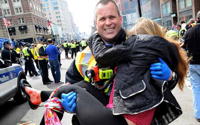 James Plourde carries a victim, since identified as Victoria McGrath, from the scene of two explosions near the Boston Marathon finish line.