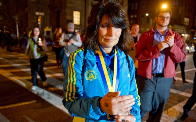 BOSTON, MASSACHUSETTS - APRIL 16: Boston Marathon qualifying runner, Bobbi Snodgrass, of Iowa, processes out of the Arlington Street Unitarian Universalist Church on her way to the Boston Public Garden during a candlelight vigil at on April 16, 2013 in Boston, Massachusetts. Snodgrass passed the finish line, missing the explosion by 3 seconds. (AP Photo/The Christian Science Monitor, Ann Hermes)