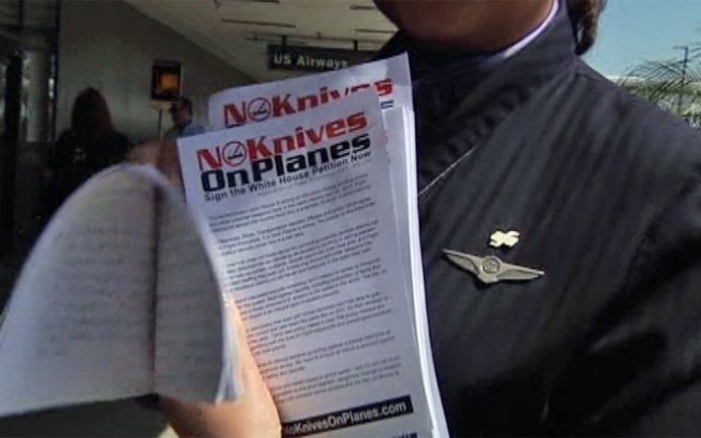 A flight attendant hands out flyers at Los Angeles International Airport on Thursday, March 21, 2013, in an effort to get public support to stop a TSA policy change that will small knives and other formerly banned items on flights.