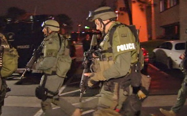 Officers from North County SWAT team walking through the campus of California State University, Fullerton, where a search was on Wednesday night for a man thought to have hidden in a classroom building after a robbery and two related car chases.