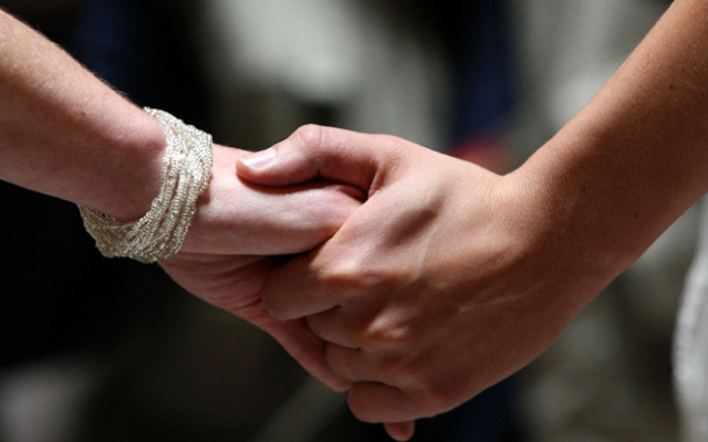 A same-sex couple hold hands as they get married.
