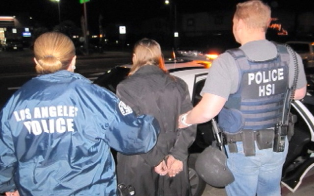 In this photo issued by ICE, a woman accused in an 11-year-old child molestation case is taken into custody in North Hills.