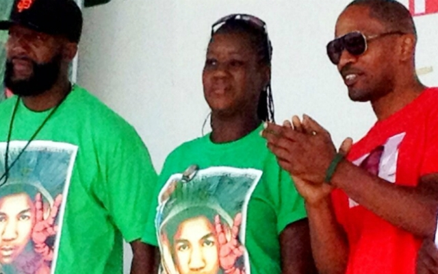 Actor Jamie Foxx, at right, is seen with the parents of slain teenager Trayvon Martin, Tracy Martin and Sybrina Fulton, during a community event Saturday in Miami.