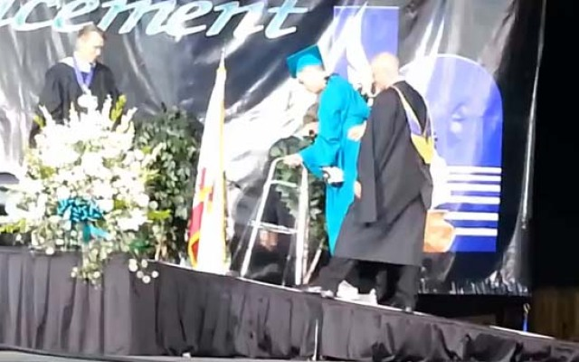 Manny Rios, who was paralyzed from the chest down in a bike accident, walks across the stage during his graduation ceremony from Sultana High School in Hesperia on May 29, 2013.