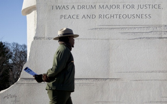 A park ranger walks past a paraphrased quote the National Parks Service plans to remove from the Martin Luther King Jr. memorial.