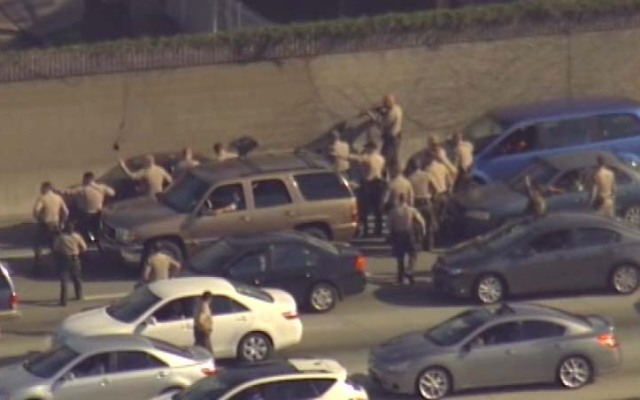 Police swarm a car on the northbound 110 Freeway as part of a checkpoint believed to be linked to a bank robbery in Moreno Valley.