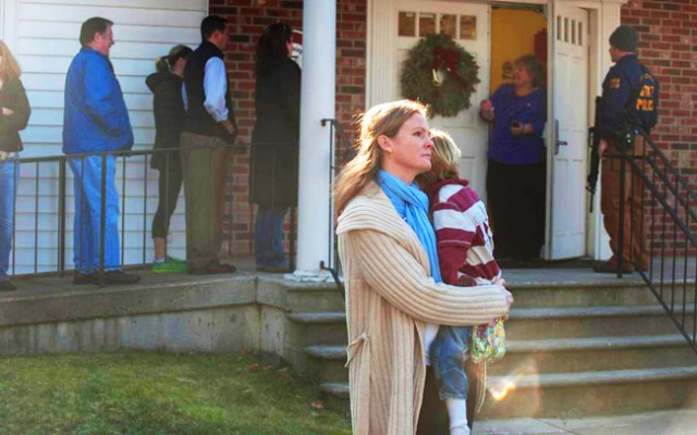 A woman holds a child as people line up to enter the Newtown Methodist Church near the the scene of an elementary school shooting on Dec. 14, 2012 in Newtown, Conn.