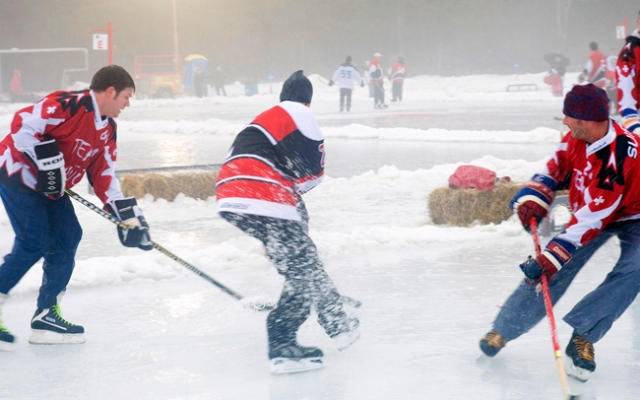Mark Cornforth, center, of the defending champion Boston Danglers, cuts between two players from Team Snuuz, of Switzerland, during the World Pond Hockey Championships in Plaster Rock, New Brunswick, Canada on February 17, 2006. Photographer: Brian Atkinson/Bloomberg News